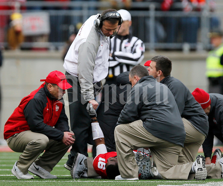 Ohio State Buckeyes head coach Urban Meyer shakes hands with Ohio State Buckeyes quarterback J.T. Barrett (16) after his injury during the fourth quarter of the NCAA football game against Michigan at Ohio Stadium on Saturday, November 29, 2014. (Columbus Dispatch photo by Jonathan Quilter)