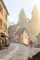 France, Aveyron, Conques, labelled Les Plus Beaux Villages de France (The Most Beautiful Villages of France), stop on El Camino de Santiago, main street in the village and Sainte Foy abbey, listed as World Heritage by UNESCO on sunrise //France, Aveyron (12), Conques, labellisé Les Plus Beaux Villages de France, étape sur le chemin de Compostelle, rue principale du village et abbatiale Sainte-Foy, classée Patrimoine Mondial de l'UNESCO au lever du soleil