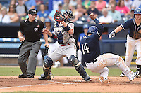 Greenville Drive catcher Austin Rei (13) attempts to make a tag as Hamlet Marte (14) slides in safely as home plate umpire Donnie Smith prepares to make the call during a game against the Asheville Tourists at McCormick Field on June 4, 2016 in Asheville, North Carolina. The Drive defeated the Tourists 6-5. (Tony Farlow/Four Seam Images)