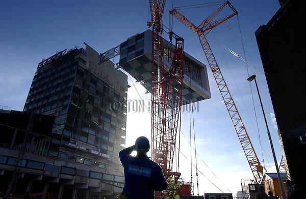 ROTTERDAM - Met hulp van zware kranen wordt een 3 etage hoge conferentiezaal  tegen het nieuwe Scheepvaart- en Transport College gehezen. Het opvallende door Neutelings Riedijk Architecten ontworpen, en door Heijmans IBC Bouw gebouwde complex krijgt op 65 meter hoogte een zaal tegen de toren 'geplakt' die als een commandopost over de stad uitkijkt. Hoewel het de bedoeling was het gevaarte tijdens de bouw bovenin op te bouwen, koos de bouwer er voor de 350 ton zware constructie op de grond te vervaardigen en dan in één keer naar boven te tillen. Uit veiligheidsoverwegingen en gewicht te besparen wordt het glas later aangebrach .COPYRIGHT TON BORSBOOM