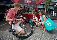NWA Democrat-Gazette/BEN GOFF @NWABENGOFF<br /> Megan Sebeck from Mojo Cycling in Bentonville shows Desmynd Castillo, 6, and sister Mariah Castillo, 7, of Siloam Springs how to change a bicycle tire Friday, July 5, 2019, during First Friday on the Bentonville Square. The theme for July was 'Great Outdoors.'