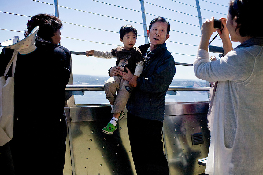 A man poses with child atop the Space Needle while having a photograph made.