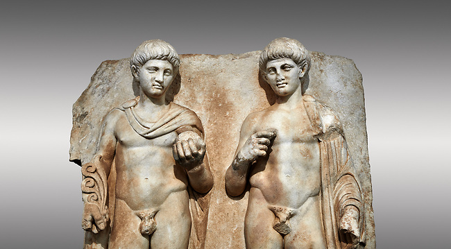 Close up of a Roman Sebasteion relief  sculpture of  Two princes, Aphrodisias Museum, Aphrodisias, Turkey.<br /> <br /> Two princes stand like statues, naked, wearing cloaks. The left figure holds the orb of the world in one hand, a symbol of  world rule that indicates he is the imperial heir, and in the other a ship's stern ornament (aphlaston), a symbol of naval victory. They and probably Gius and Lucius, the grandsons of Augustus, or Nero and Britanicus, Claudius' heir.