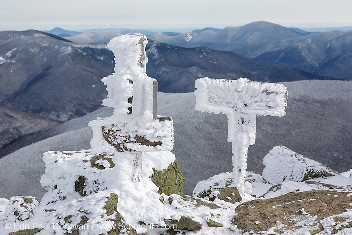 Trail signs on the summit of Mount Lafayette covered in snow during the winter months in the White Mountains, New Hampshire. The Appalachian Trail (Franconia Ridge Trail) travels over the summit of this mountain.