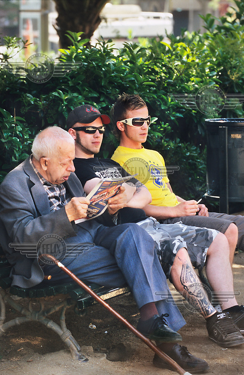 Two young men wearing sunglases and with a tattoo share a bench with an old man...