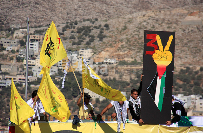 Palestinian students supporters of the Fatah movement wave with the party flag during the celebration of the student council elections at al-Najah University in the West Bank town of Nablus, Monday, Nov. 8, 2010. Photo by Wagdi Eshtayah