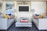 A television stands in a niche above built-in cupboards and a book shelf in this top floor sitting room