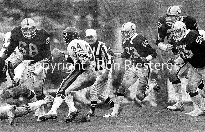 Chicago Bears Walter Payton running against the Oakland Raiders..#68 Johnny Robinson, Odis McKinney, John Matuszak, and Matt Millen. (1981 photo/Ron Riesterer)