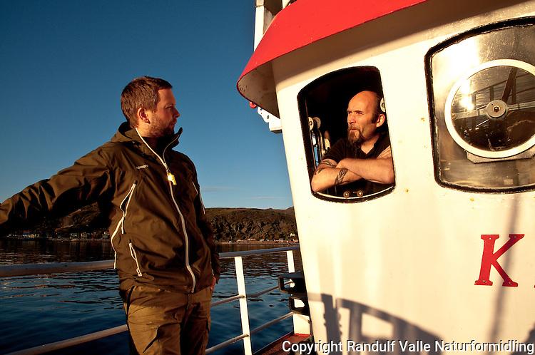 To menn prater sammen på fiskebåt i nydelig kveldssol. ---- Two men talking on boat in evening sun.