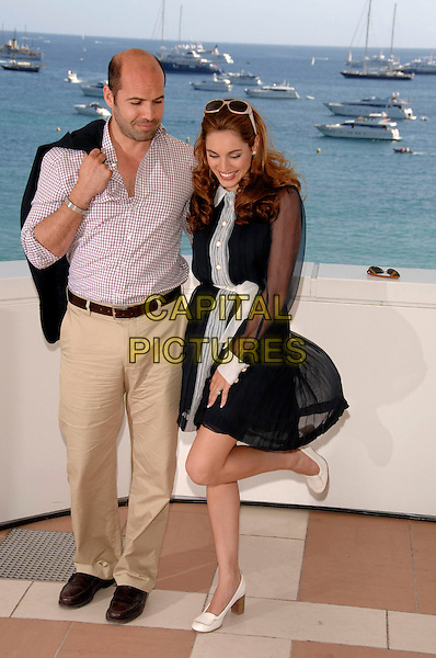"""BILLY ZANE & KELLY BROOK.Photocall for """"Fishtales"""" starring Kelly as a mermaid at the  60th International Cannes Film Festival, Cannes, France.  May 17th , 2007.full length sunglasses shades black sheer sleeves dress white stripe sash collar belt beige trousers red plaid shirt couple leg up.CAP/PL.©Phil Loftus/Capital Pictures."""