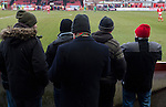 Altrincham 2 Worcester City 0, 23/03/2013. Moss Lane, Blue Square Bet North. Five spectators wearing woollen hats watching the action during the second-half of the the Blue Square Bet North fixture between Altrincham (in red) and Worcester City at Moss Lane, Altrincham. The home team won the match 2-0 watched by 777 spectators on a day when most non-League football in England was cancelled due to adverse weather. Altrincham were historically one of the major English non-League teams but have never been promoted to the Football League. Photo by Colin McPherson.