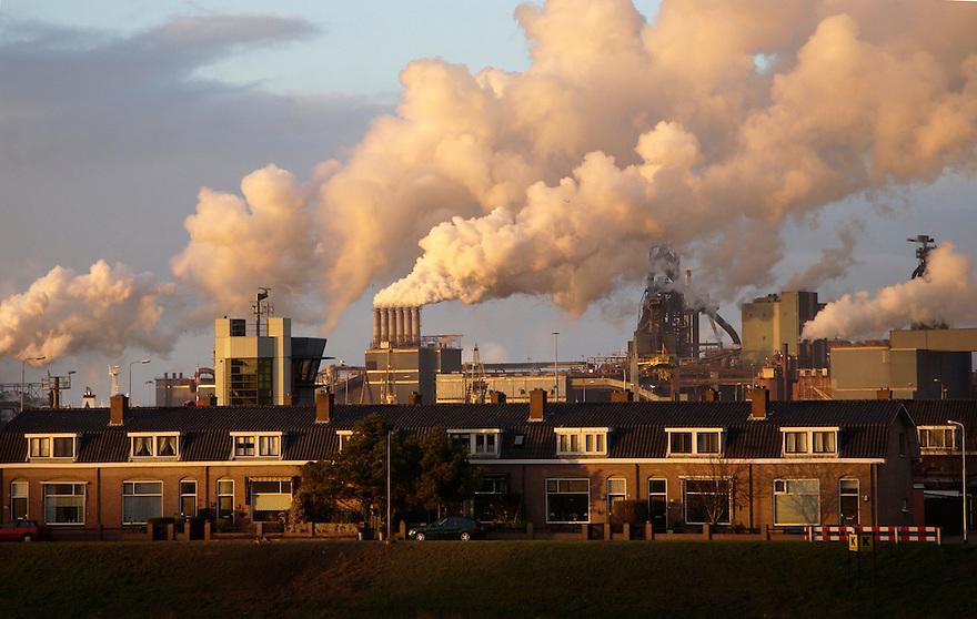Nederland, Ijmuiden, 25 jan 2004.Corus, hoogovens, gezien vanaf IJmuiden. Veel rook uit schoorstenen van de grootste luchtvervuiler van het land. Een rijtje huizen op de voorgrond..Industrie, staal, luchtvervuiling, uitstoot, co2, ..Foto (c) Michiel Wijnbergh/Hollandse Hoogte