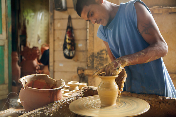 Young Indo-Trini man (Ryan Lall) at a potter's wheel ,making a clay pots and deyas at Radika pottery in Chaguanas