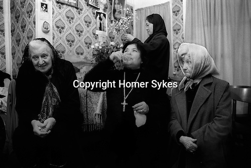 Woman drinking Holy water from well outside of house. Mrs Nora Arthurs, a Catholic Voice-Box, Seer and Mystic, in her home on Canvey Island, Essex UK conducting a prayer meeting. 1996