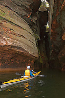 A sea kayaker explores the sea caves at Meyers Beach in the Apostle Islands National Lakeshore near Bayfield Wisconsin.