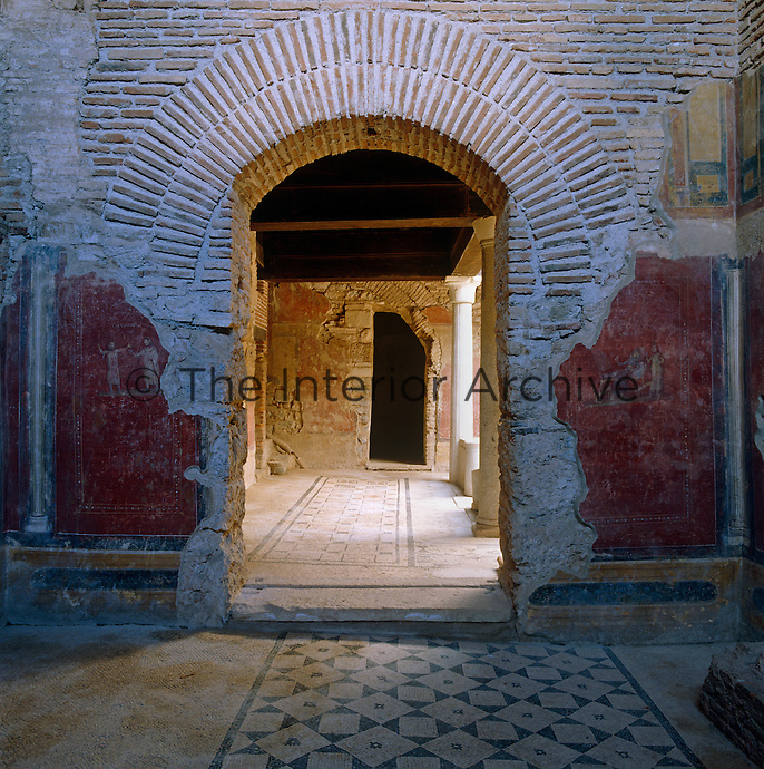 View through a brick archway in a wall with the remains of a fresco to a columned courtyard
