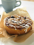 Single sticky bun topped with icing on parchment paper and cup of coffee.