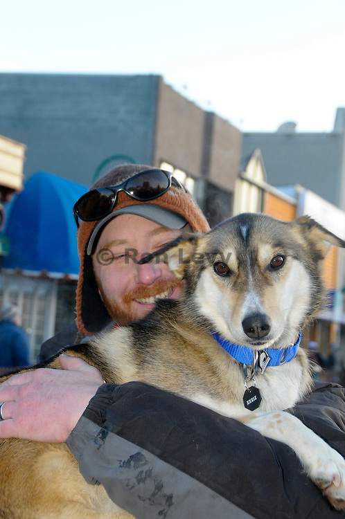 Iditarod musher Justin Savidis and one of his sled dogs, Nattie, before the start of Iditarod 2011. Anchorage, AK