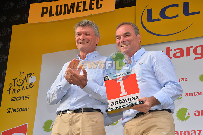 Former winners Bernard Thevenet presents Bernard Hinault with the combativity award on the podium after Stage 9 of the 2015 Tour de France a team time trial running 28km from Vannes to Plumelec, France. 11th July 2015.<br /> Photo: ASO/B.Bade/Newsfile