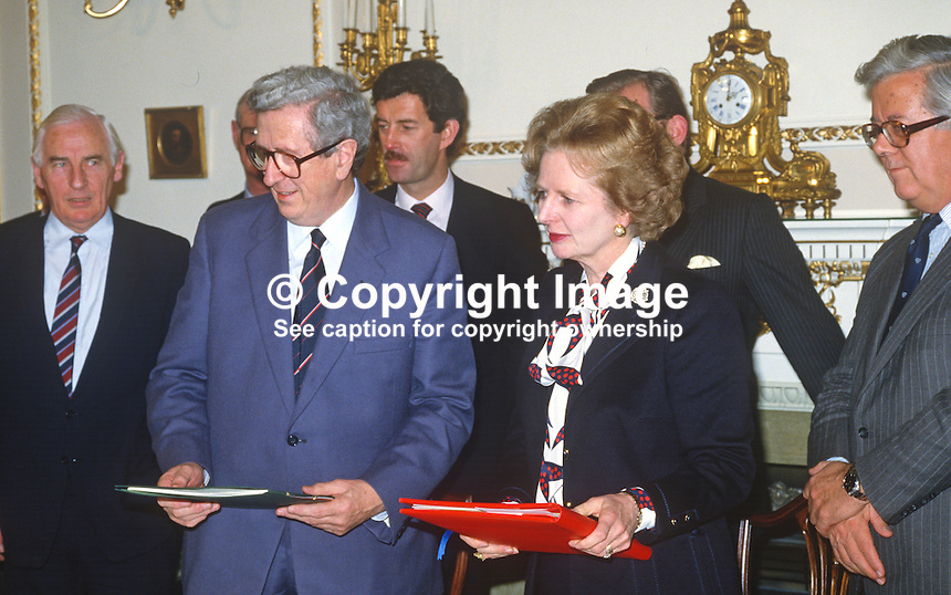 Margaret Thatcher, Prime Minister, UK, and Garret Fitzgerald, Prime Minister, An Taoiseach, Rep of Ireland, hold signed copies of the Anglo-Irish Agreement at Hillsborough Castle, N Ireland, 15th November 1985.1985111505k.<br />