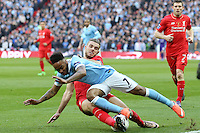 Raheem Sterling of Manchester City is tackled by Daniel Sturridge of Liverpool during the Capital One Cup match between Liverpool and Manchester City at Wembley Stadium, London, England on 28 February 2016. Photo by David Horn / PRiME Media Images.