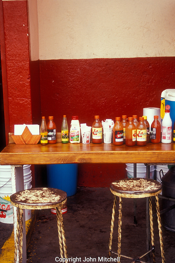 Bottles of hot sauce on the counter of a comedor restaurant in San Miguel de Allende, Mexico