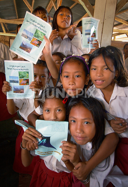 Happy kids with RARE Pride booklets, Komodo Village, Komodo National Park