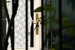 A golden door handle on a white door in Menaggio on Lake Como, Italy.