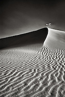 Black and white image of sand blowing off the crest of a sand dune at White Sands National Monument, with textured ripples in the foreground.