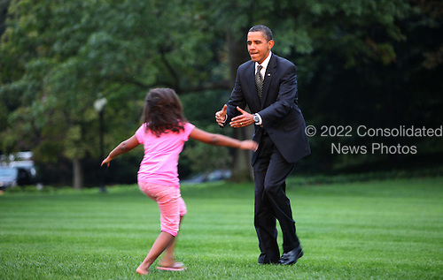 Washington, DC - September 15, 2009 -- United States President Barack Obama gets a warm welcome home from daughter Sasha on the South lawn of the White House on September 15, 2009.  .Credit: Dennis Brack / Pool via CNP