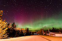 A brilliant Northern Lights display amongst the glow of a street light and paved street. Marquette County, Michigan