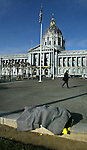 A homeless man sleeps on the sidewalk covered in a blanket with San Francisco's City Hall in the background.
