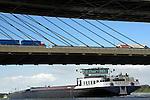 ZALTBOMMEL - Een Nederlands binnenvaartschip met vracht vaart over de rivier de Waal onder de betonnen Martinus Nijhoff-brug - en een stalen spoorbrug - door waar geladen vrachtwagens op de snelweg op pad zijn voor bevoorrading. COPYRIGHT TON BORSBOOM