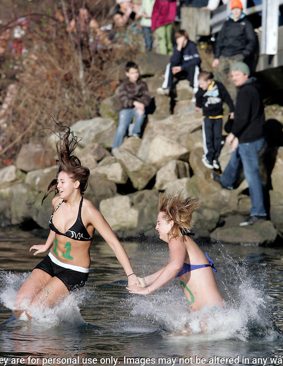 Two girls hit the icy waters during the 27th annual Polar Bear jump into the Burley Lagoon in Olalla, Washington on January 1, 2011. Over 300 hardy participants  braved the chilly lagoon waters to join in on the annual New Year's Day Tradition.  ©2011. Jim Bryant. All Rights Reserved.