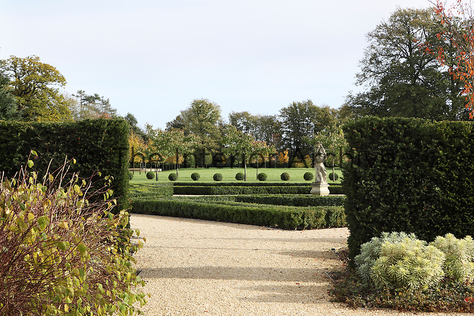 View through a neatly clipped hedge towards  open lawns and a box hedge garden
