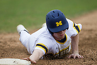 Michigan Wolverines shortstop Travis Maezes (9) dives back to first base during the NCAA baseball game against the Washington Huskies on February 16, 2014 at Bobcat Ballpark in San Marcos, Texas. The game went eight innings, before travel curfew ended the contest in a 7-7 tie. (Andrew Woolley/Four Seam Images)