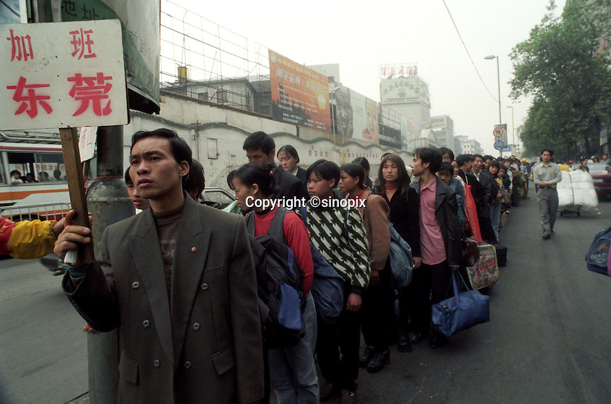 Officials direct a group of migrants just arrived from northern China outside Guangzhou railway station. Illegal job agencies often prey on ignorant jobseekers. Some 200,000 migrants pass through the station daily..06-MAR-99