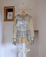 "A shimmering silver tunic designed for the Ballet ""Thamar"" in 1912, its scalloped edges and pointy cuffs creased with age over a faded yellowing shirt"