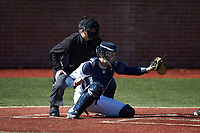 Wingate Bulldogs catcher Logan McNeely (18) sets a target as the home plate umpire looks on during the game against the Concord Mountain Lions at Ron Christopher Stadium on February 2, 2020 in Wingate, North Carolina. The Mountain Lions defeated the Bulldogs 12-11. (Brian Westerholt/Four Seam Images)