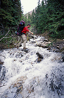 CANADA, ALBERTA, KANANASKIS, MAY 2002. A hiker crosses Elbow Creek. The Kananaskis Country provincial park is home to Canada's most beautiful nature and wildlife. It has also escaped the mass tourism as in Banff National Park. Photo by Frits Meyst/Adventure4ever.com