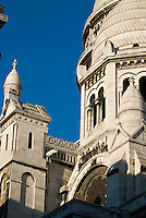 Sacre Coeur Basilica, Paris.  Shot in the morning with a blue,cloudless sky.  Photo shows the details of two towers and spires.  One of the Rose Windows is also prominent.
