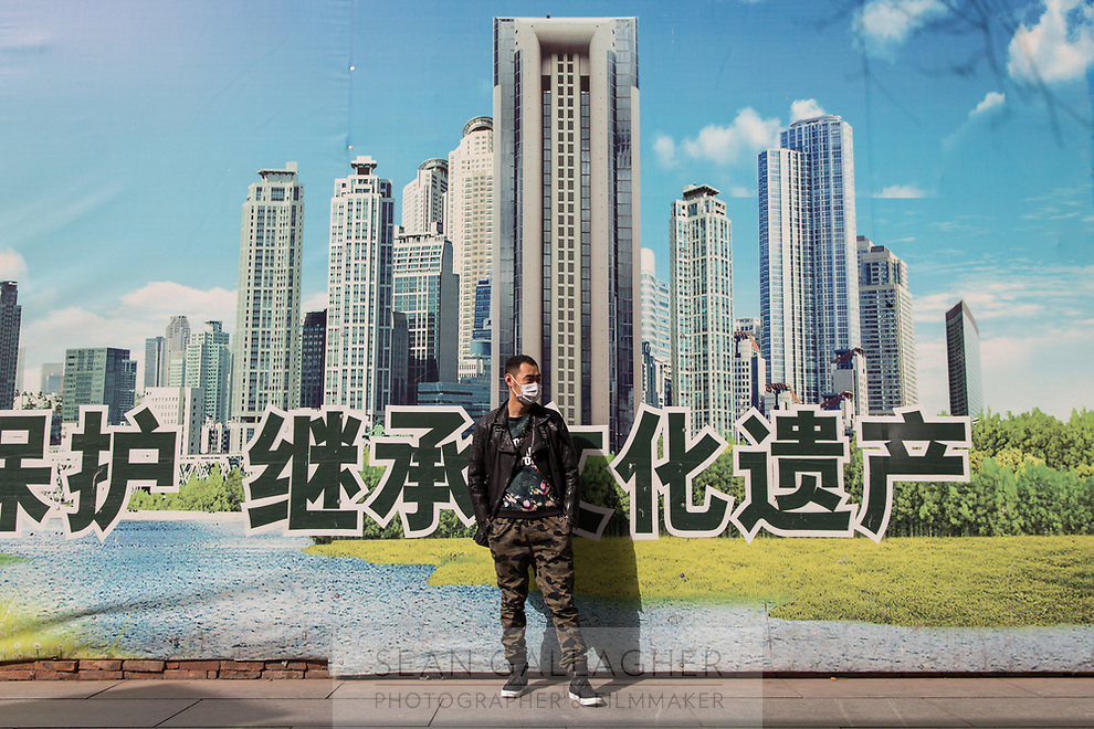 """Cao (34), a young businessman from China's north-western Heilongjiang province, stands near an advertisement in Beijing's Xidan shopping district. """"Beijing's dust is just too much"""", Cao says as he visits the city for a holiday with his friend. """"At home, there are blue skies and white clouds!""""  PM2.5 reading - 102 - Unhealthy for Sensitive Groups"""