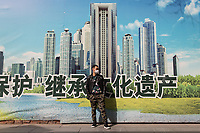 "Cao (34), a young businessman from China's north-western Heilongjiang province, stands near an advertisement in Beijing's Xidan shopping district. ""Beijing's dust is just too much"", Cao says as he visits the city for a holiday with his friend. ""At home, there are blue skies and white clouds!""  PM2.5 reading - 102 - Unhealthy for Sensitive Groups"