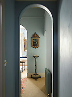 The hallway walls are decorated in a pale blue and the flooring is neutral carpeting.