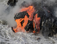 Lava Split: Molten lava splits away from this lava ledge and falls into the ocean, Kamokuna, Hawai'i Volcanoes National Park, Big Island.