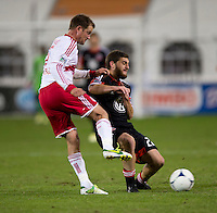 Chris Korb (22) of D.C. United collides with Teemu Tainio (6) of New York Red Bulls during the game at RFK Stadium in Washington DC. D.C. United tied New York Red Bulls, 1-1.