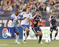 New England Revolution midfielder Benny Feilhaber (22) brings the ball forward as Montreal Impact midfielder Collen Warner (18) closes. In a Major League Soccer (MLS) match, Montreal Impact defeated the New England Revolution, 1-0, at Gillette Stadium on August 12, 2012.