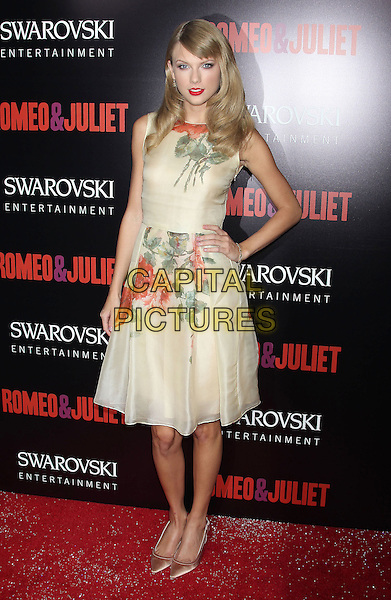 Taylor Swift<br /> &quot;Romeo &amp; Juliet&quot; Los Angeles Premiere held at Arclight Cinemas, Hollywood, California, USA.<br /> September 24th, 2013<br /> full length floral hand on hip yellow red green print dress sleeveless <br /> CAP/ADM/RE<br /> &copy;Russ Elliot/AdMedia/Capital Pictures