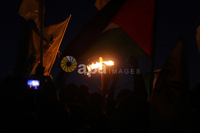 Palestinian supporters of Fatah movement hold the party's torch during a rally in Gaza city on December 31, 2012. The Gaza branch of Palestinian president Mahmud Abbas's Fatah party said on Friday it will mark its anniversary in the Hamas-ruled enclave after an accord between the two factions. Photo by Majdi Fathi