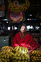 India - Manipur - Imphal - Oinam Victoria 48 years old, from Langthabal Awang Leikai.We put incense on top of bananas, to chase away evil spirits and keep the business profitable for the entire day. She has been working here for three years. It's her mother in law's place, she inherited it. When there is a funeral or a marriage, when we have to (have bananas), or for the worshipping of god. For that, we can't have odd numbers, whatever we offer to the god should be in even numbers. Odd numbers is for eating. And you can't remove one banana, it has to be even from the plant itself. Generally women who have the lowest income in the family are given the stalls. The mother chooses, even the husband won't). Topics she talks about at market: family matters, ups and downs of business, friends she has not seen in years… At home we are not that open to speak openly. Here is open space, we openly discuss.